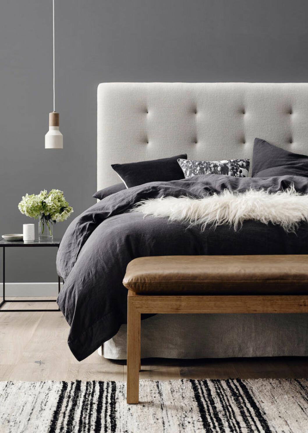 Säng med mörka textiler, grå sänggavel och en bänk framför