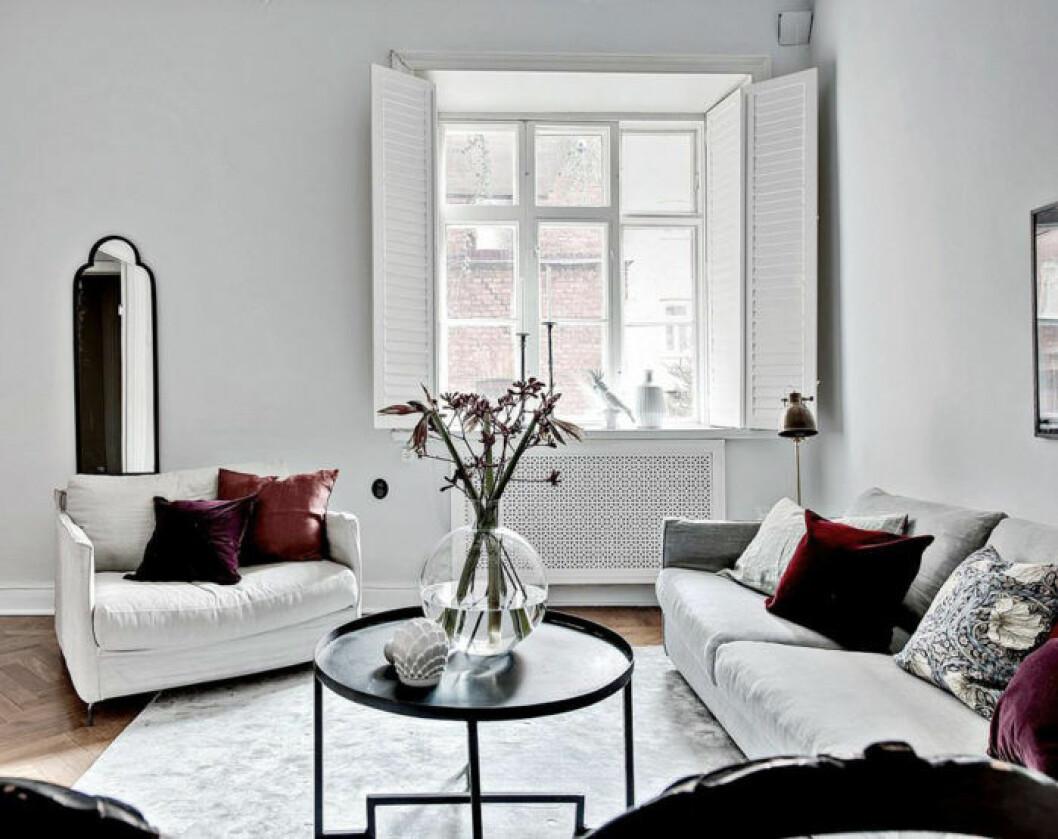 Vitmålat vardagsrum med lila kuddar