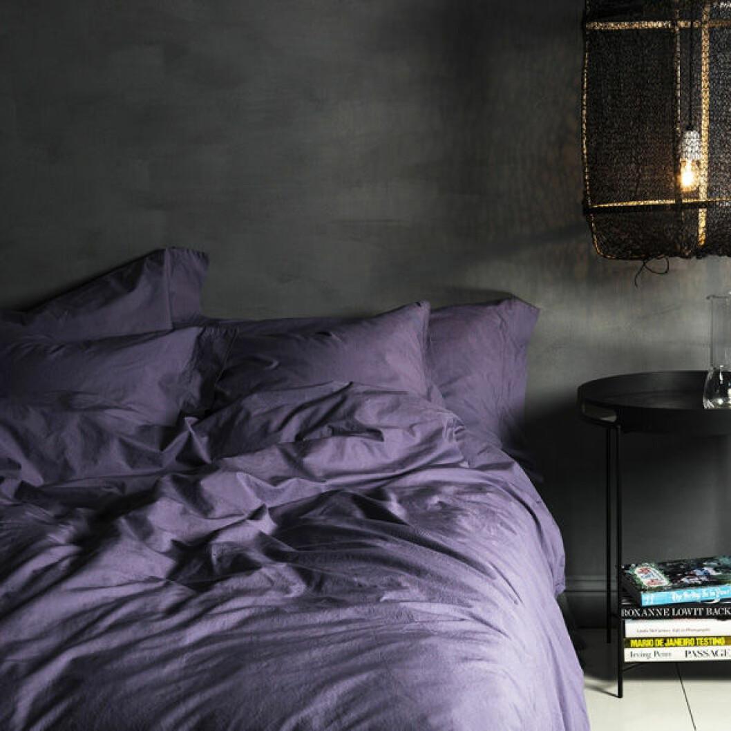 Mörk sovrum med säng bäddad med violfärgade lakan.