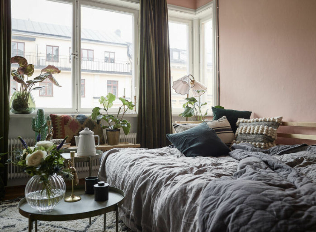 Cozy bed and pink painted walls. Scandinavian interior decoration ideas and inspiration.
