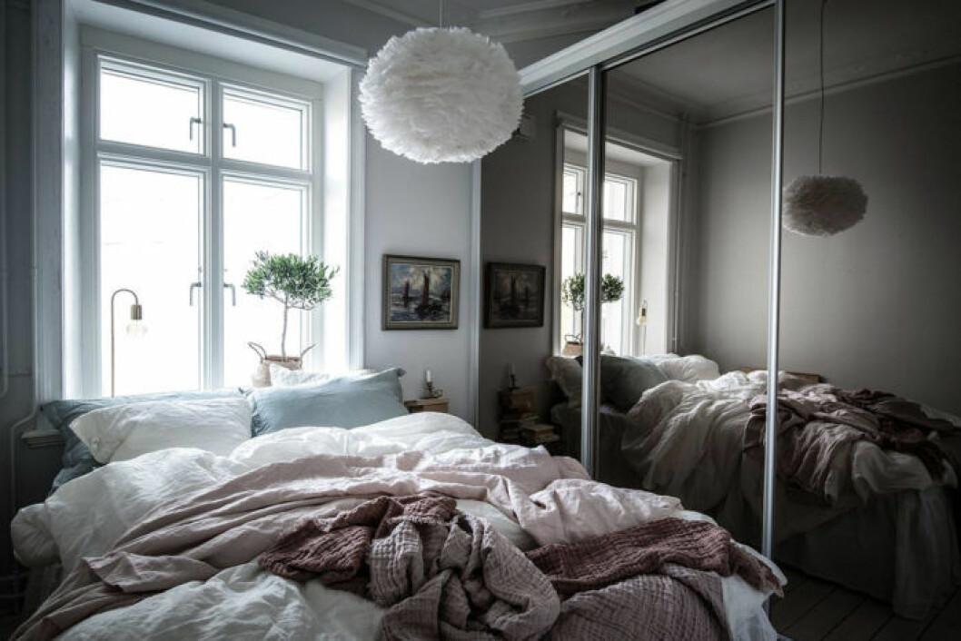 Sovrum med garderob som har spegeldörrar i rökfärgat spegelglas