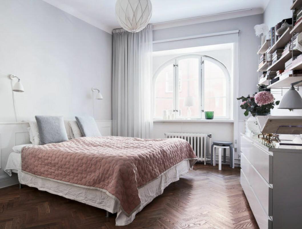 Sovrum med rosa överkast och väggfasta hyllor
