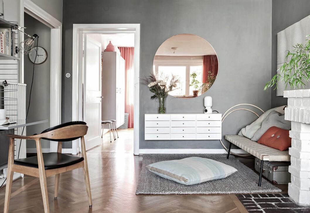 Gråmålad vägg i vardagsrum. Rund tonad spegel, dagbädd från Ikea och hyllsystem från String.