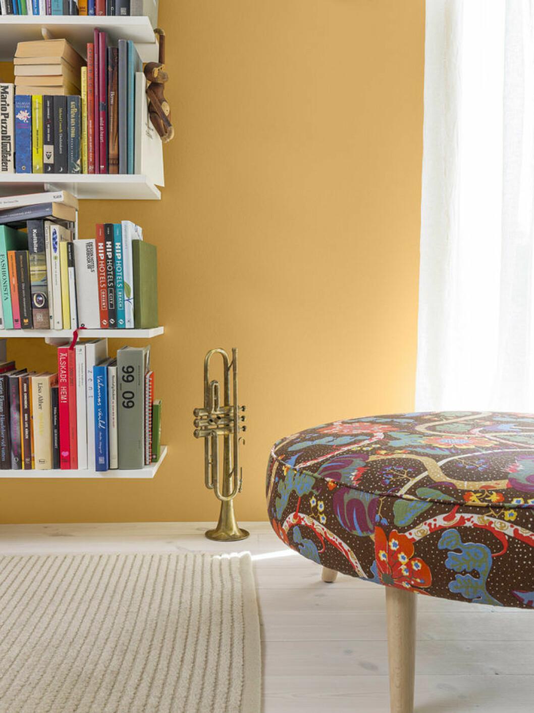 Gulmålad vägg, bokhylla och mönstrad pall