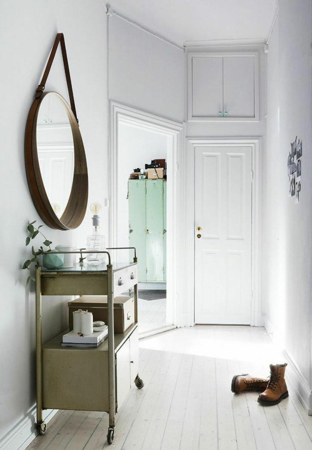 Hall med stor rund spegel och litet avlastningsbord
