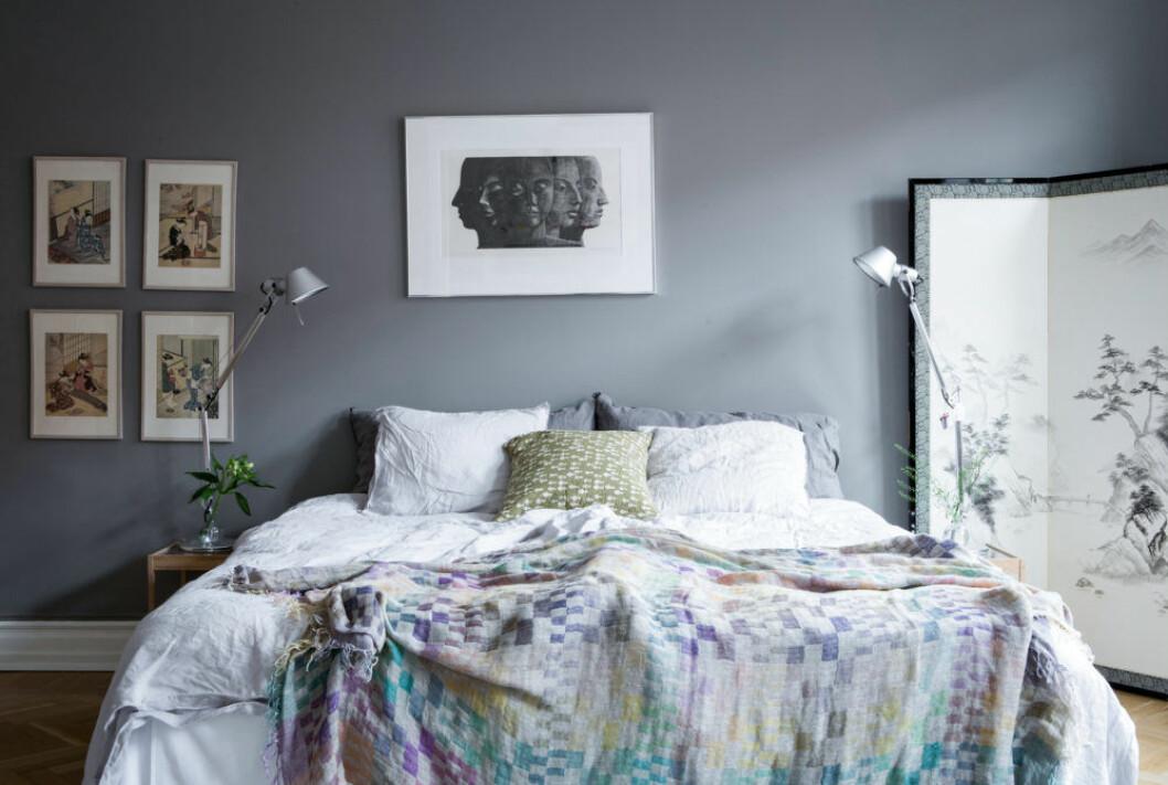 Sovrum med gråa väggar och en säng bäddad med skira multifärgade tyger och kuddar