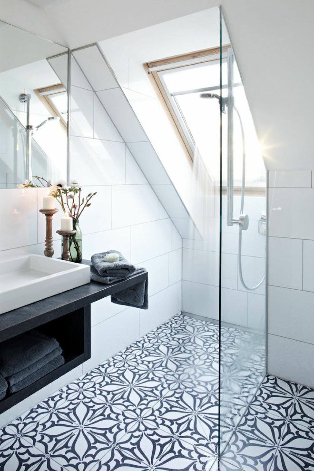 Badrum med mönstrat kakel på golvet mot enkla, vita plattor på väggen.