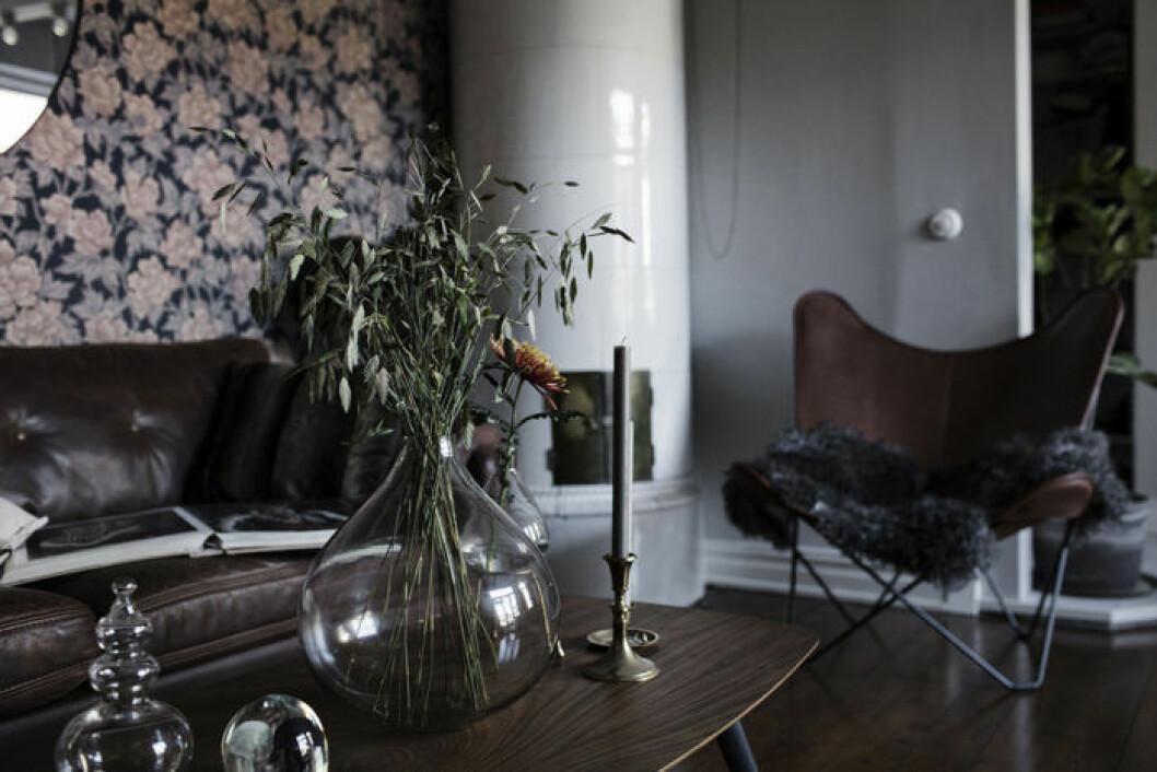 Detaljbild på ett mörkt träbord med yvig bukett i en vas
