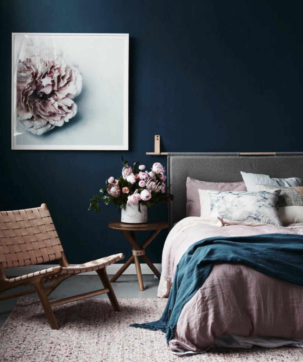 Sovrum med blåa väggar och rosa pioner i en vas på sängbordet