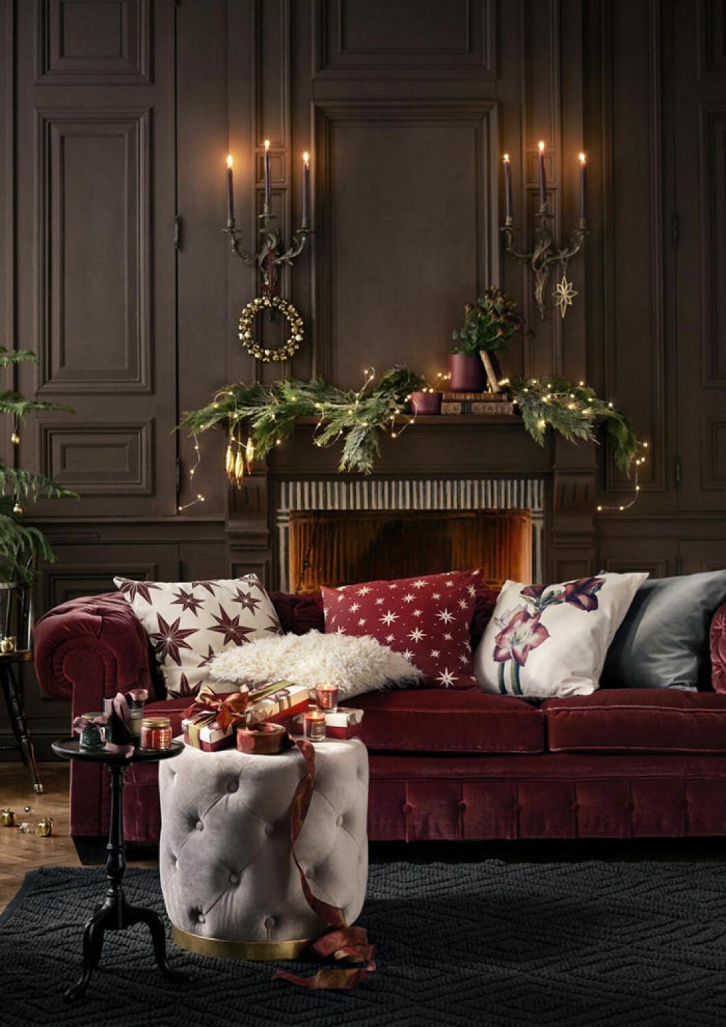 Vardagsrum med julstämning och en röd sammetssoffa i mitten