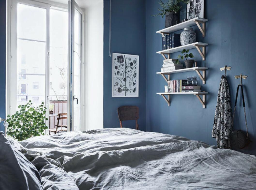 Sovrum med blåa väggar, vägghylla och ljusblåa textilier