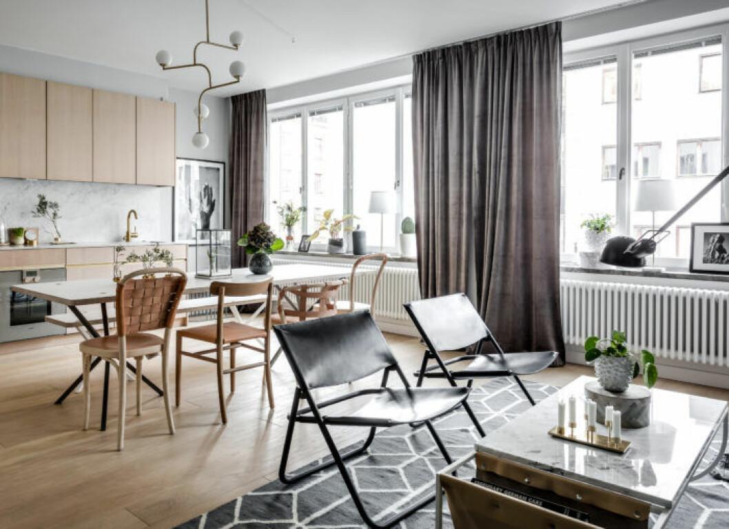 Kombinerat kök och vardagsrum med gardinstängerna högt upp