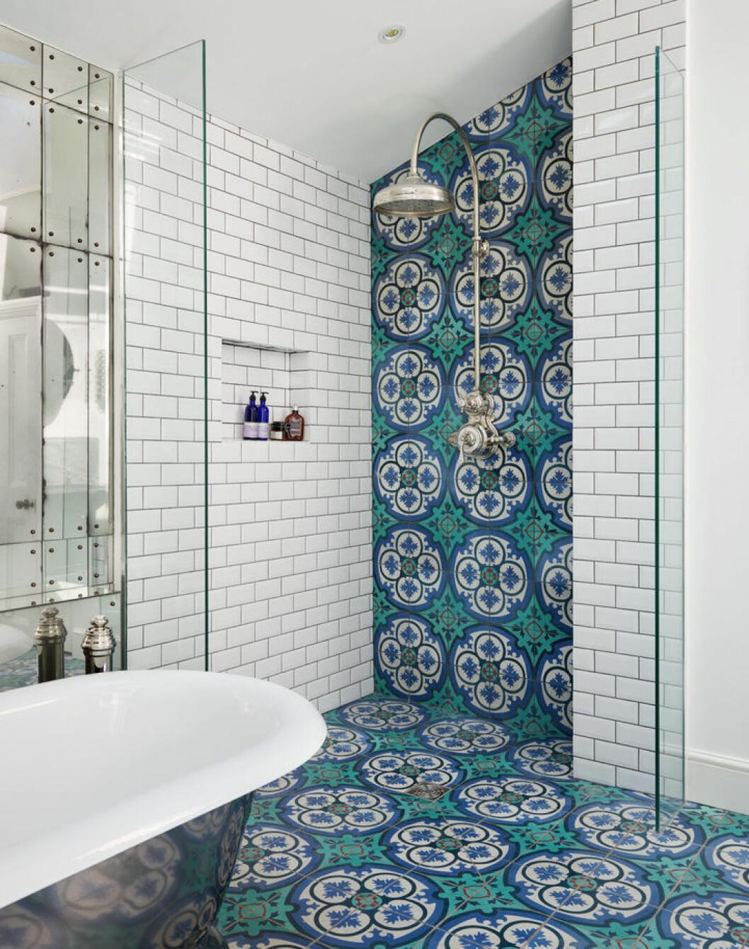Färgstarkt, mönstrat kakel på golvet i ett badrum löper upp på ena duschväggen.