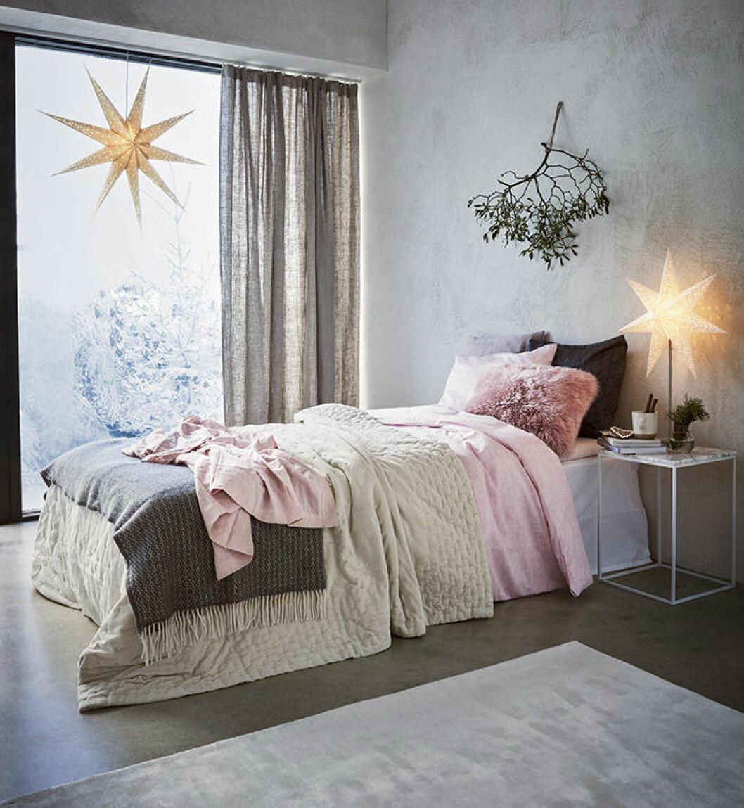 Sovrum med julstjärnor och vacker bäddning i rosa toner.