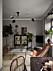 Stilsäkert vardagsrum med träd, växter och fladdermusstolen. Svart och designmässig taklampa och marmorbord. Vitrinskåp på ben.