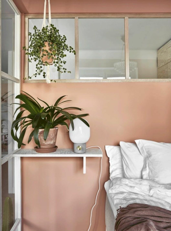 En hylla istället för sängbord i ett compact living-sovrum.