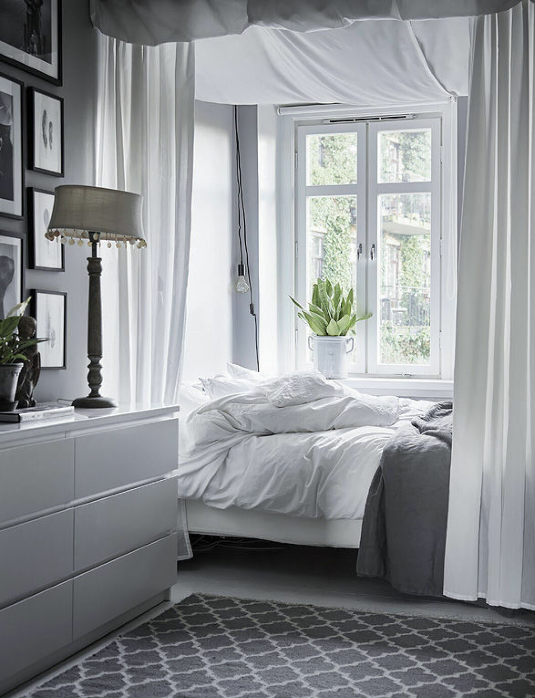 Cosy bedroom with grey and white colours. Fabric over the bed. Scandinavian interior decoration ideas and inspiration.