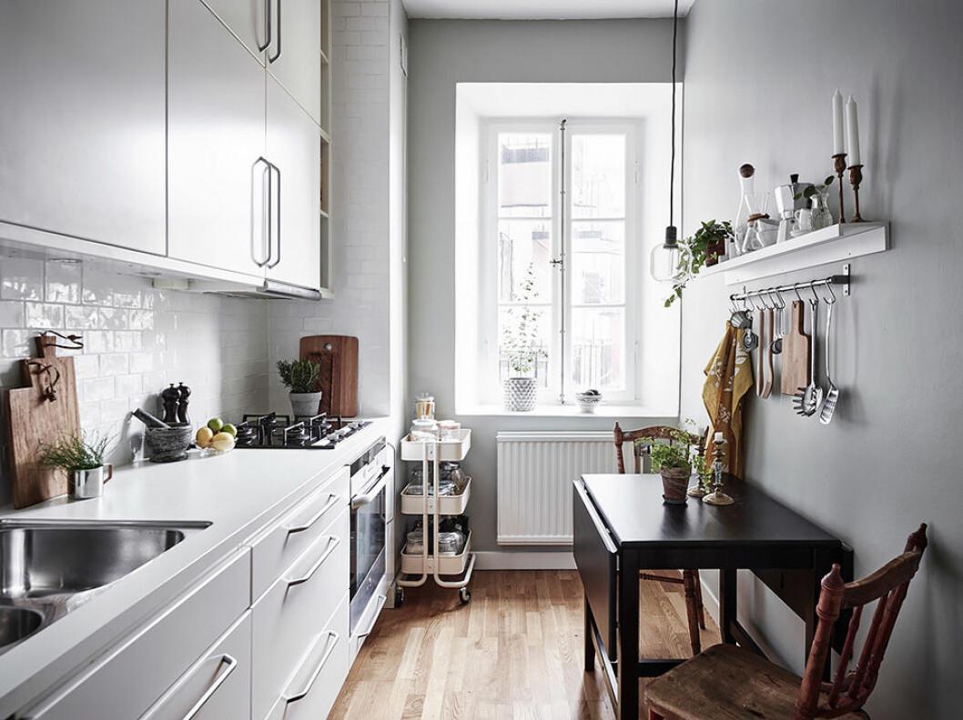 Långsmalt kök med ett smalt avlångt bord längs ena väggen