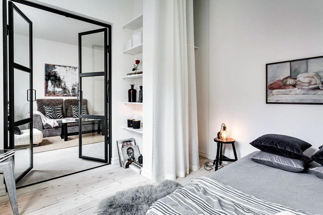 Glasvägg med pardörrar leder från sovrum till vardagsrum