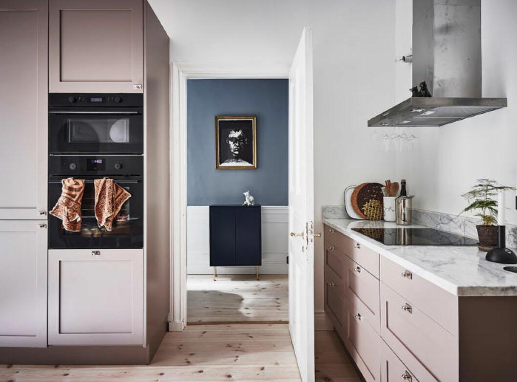Rosa köksluckor och en vy mot ett rum med blå väggar