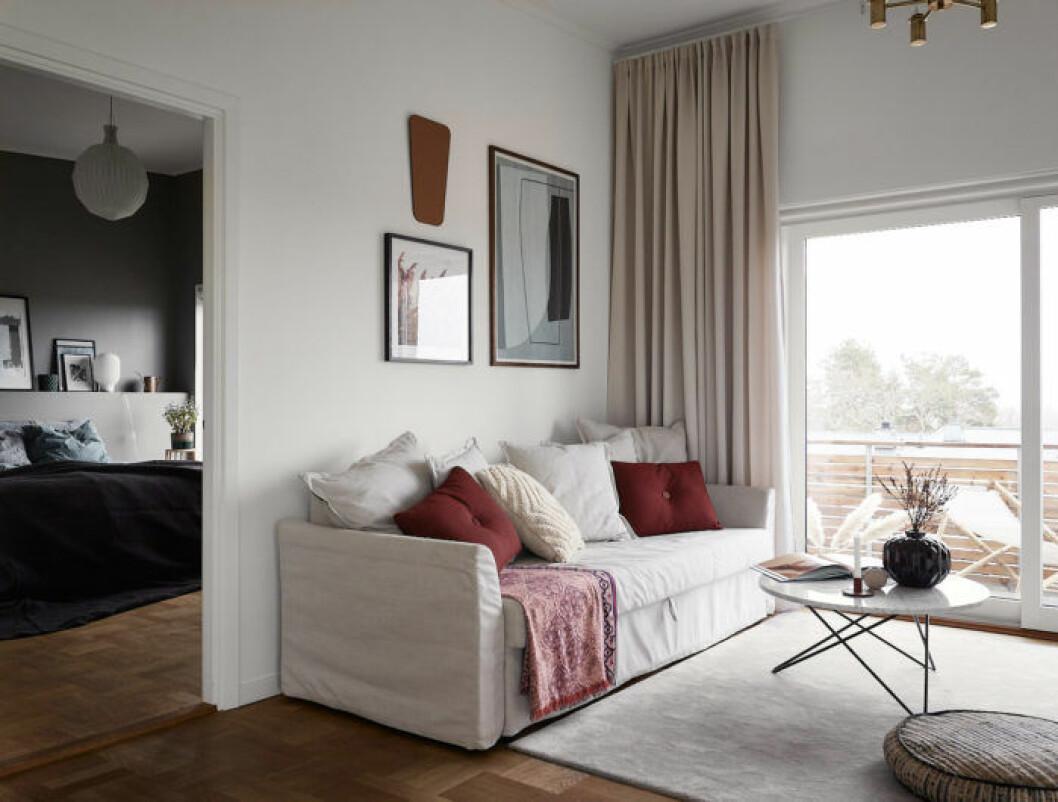Ljust vardagsrum med gardiner och en mysig soffa