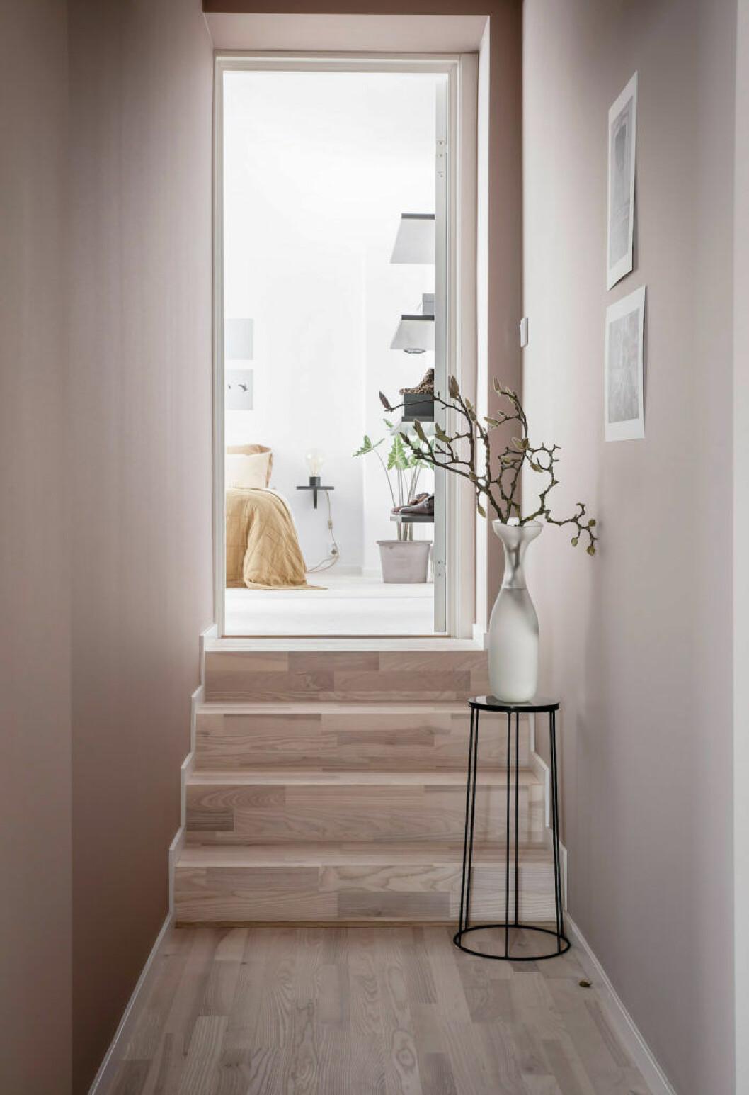 Ljusrosa väggar, trägolv och trappa i trä som leder upp till sovrummet
