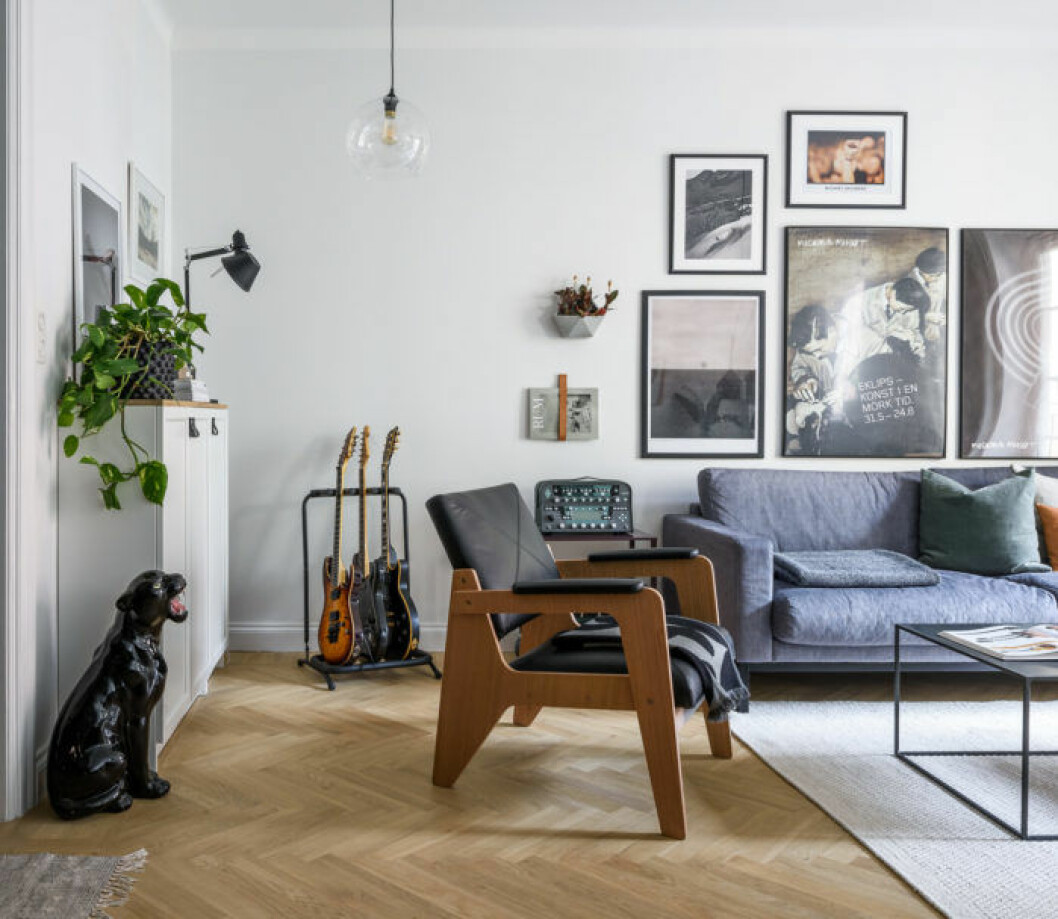 Vardagsrum med prydnadspanter, stol i läder och trä och blå soffa. Tavelvägg och gröna växter.