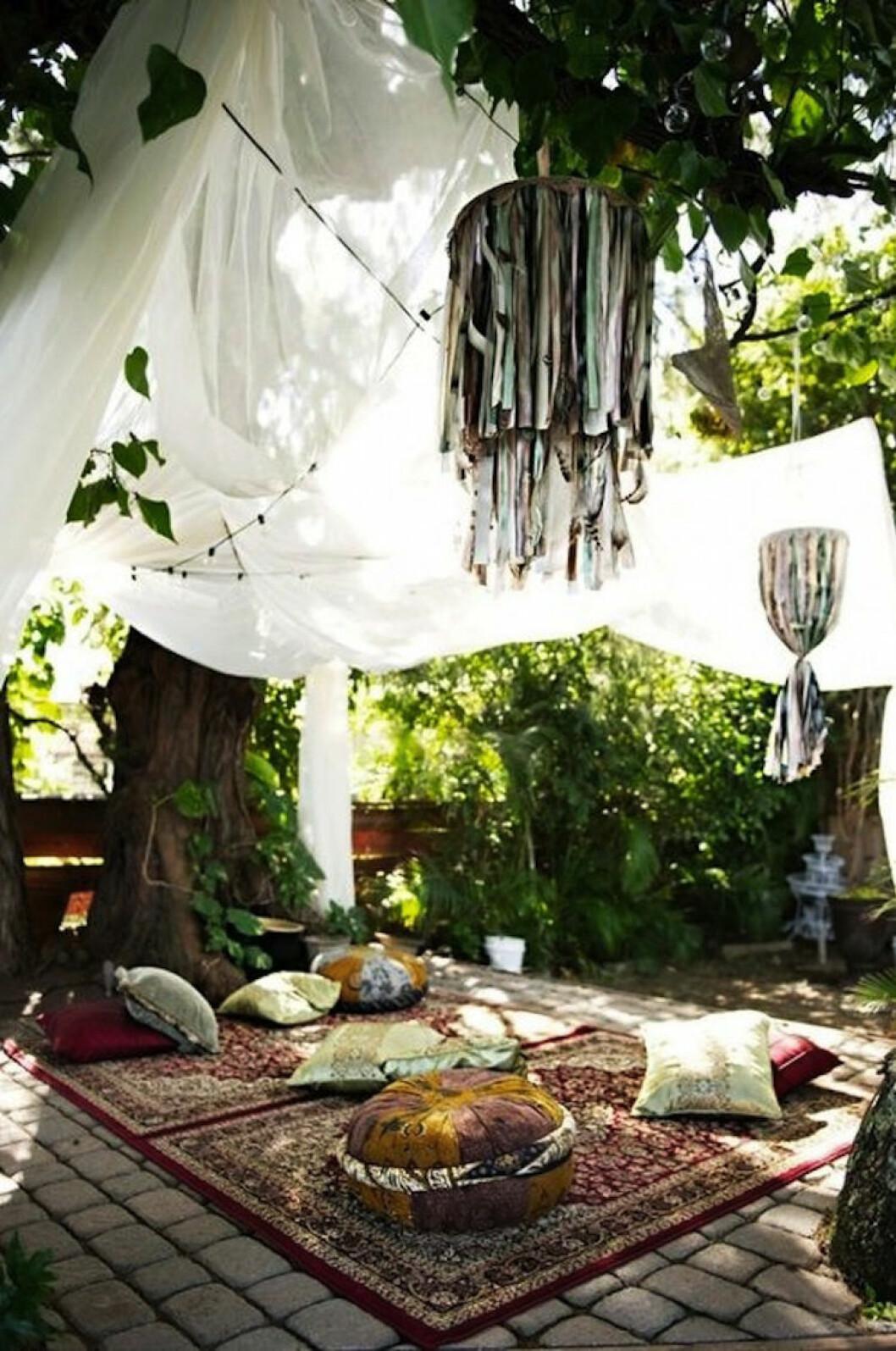 Pyntad trädgård med stora textilier i träden