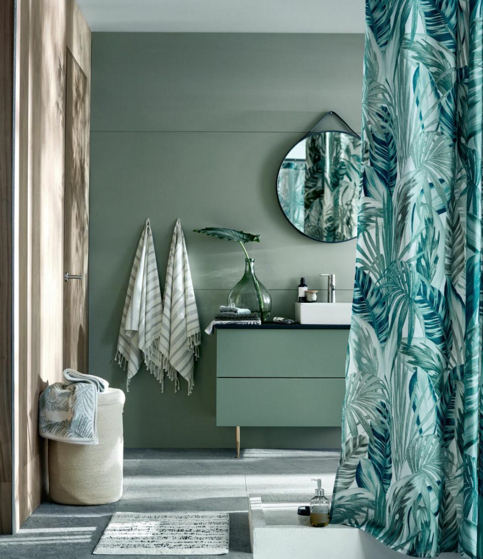 Badrum i grönt, grönt duschdraperi och rund spegel.