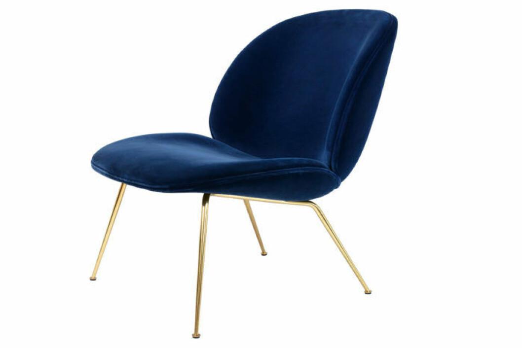 Loungestol i mörkblå sammet och med ben i mässin