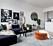 Ljust vardagsrum bryts av med svart soffa med färgglada kuddar