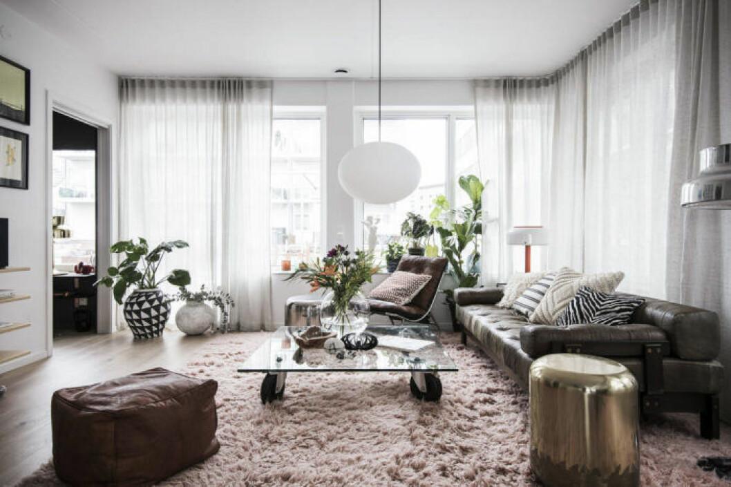 Vardagsrum med rosa ryamatta och skinnsoffa samt sittpuff.