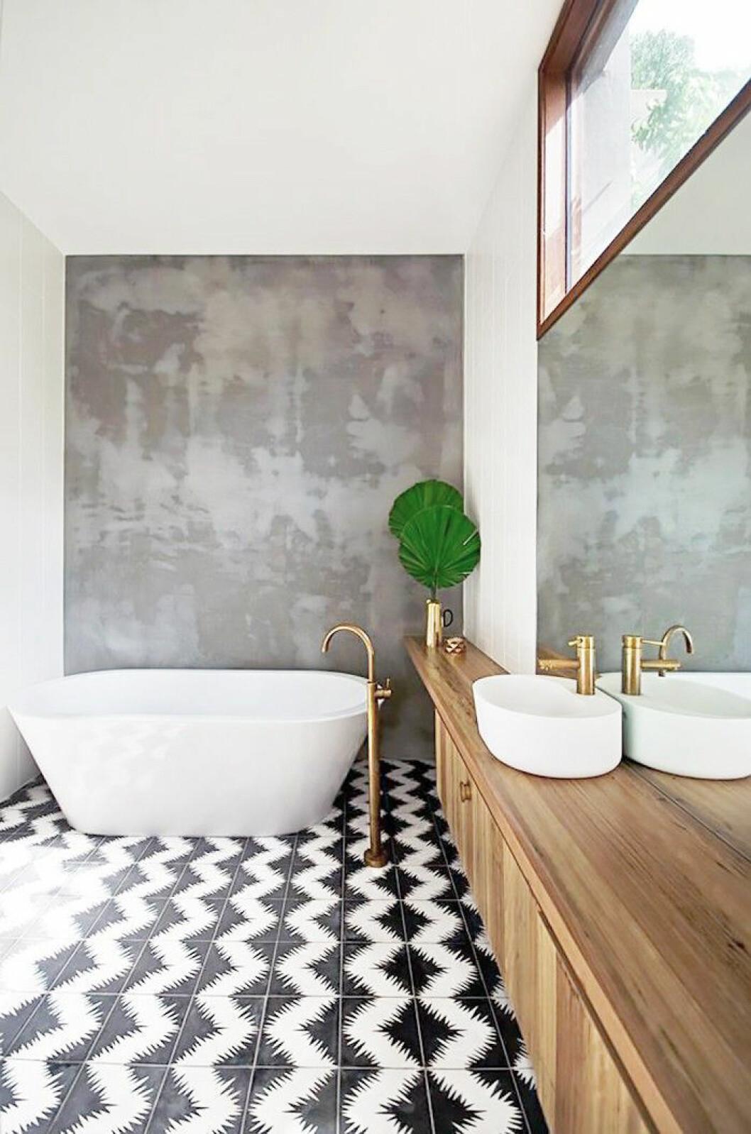 Svart/vitt klinker på golvet mot betongvägg i ett badrum.