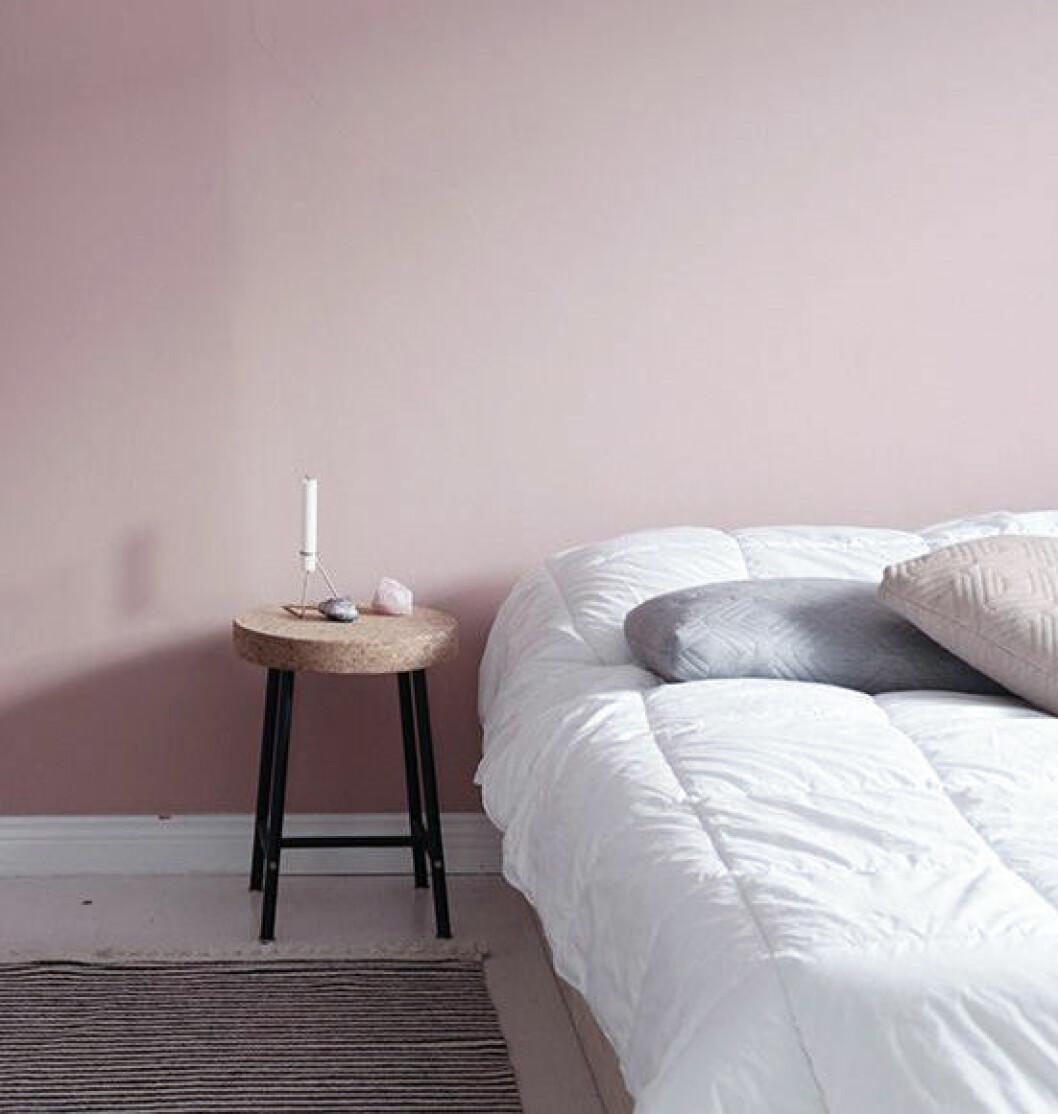 Sovrum med väggar målade i en varm ljusrosa nyans.