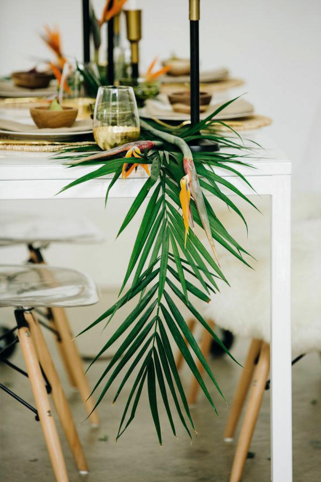 en tropisk dukning med palmblad som löpare