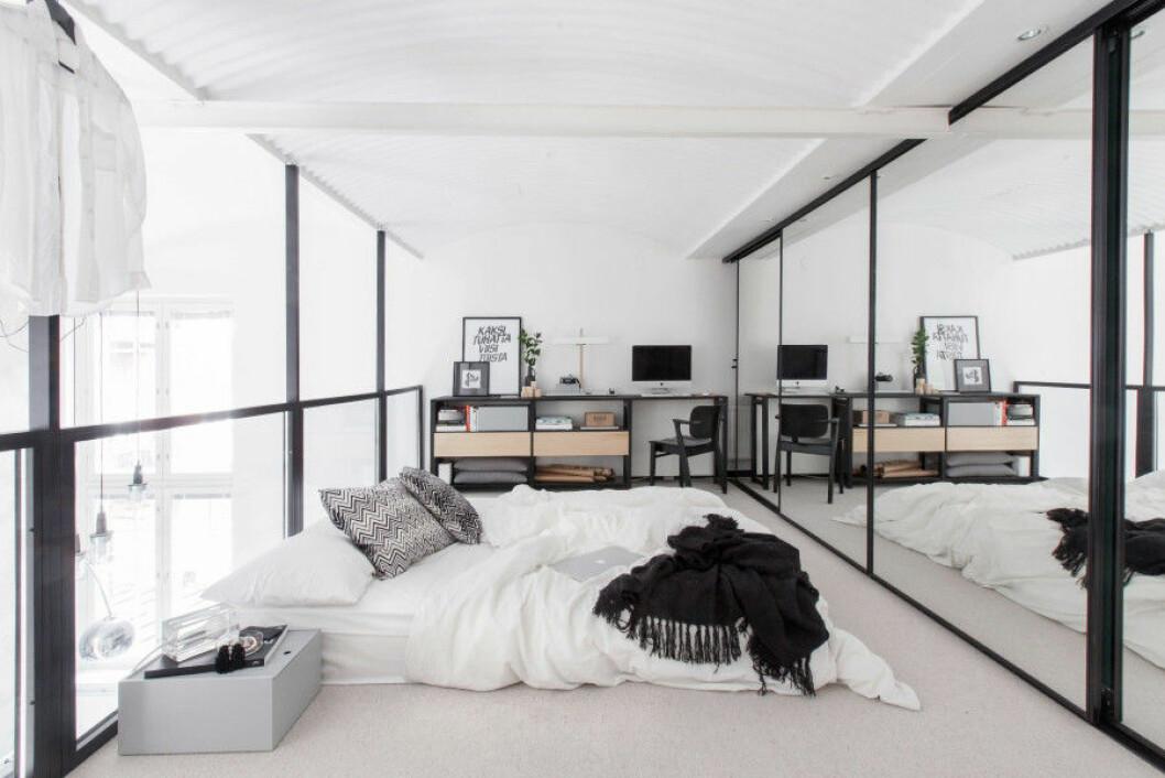 Glasväggar skärmar av loftet där sängen är placerad