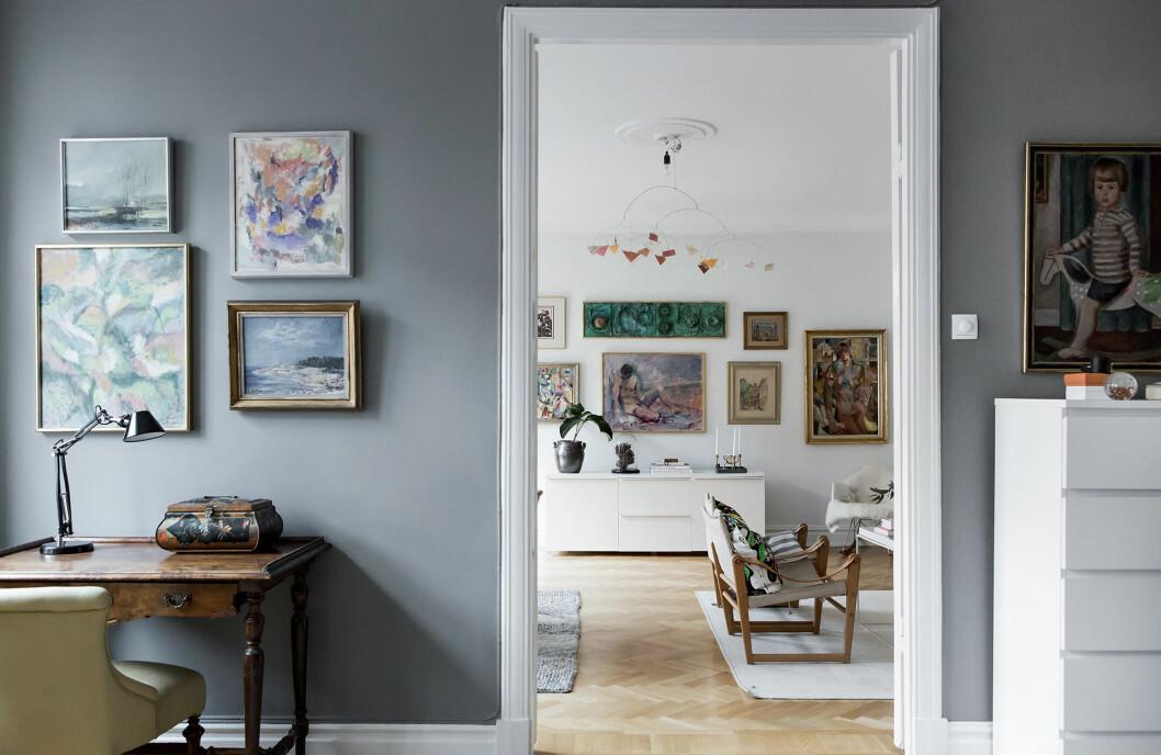 Grå matt vägg med tavlor. Tavelvägg och oljemålningar.