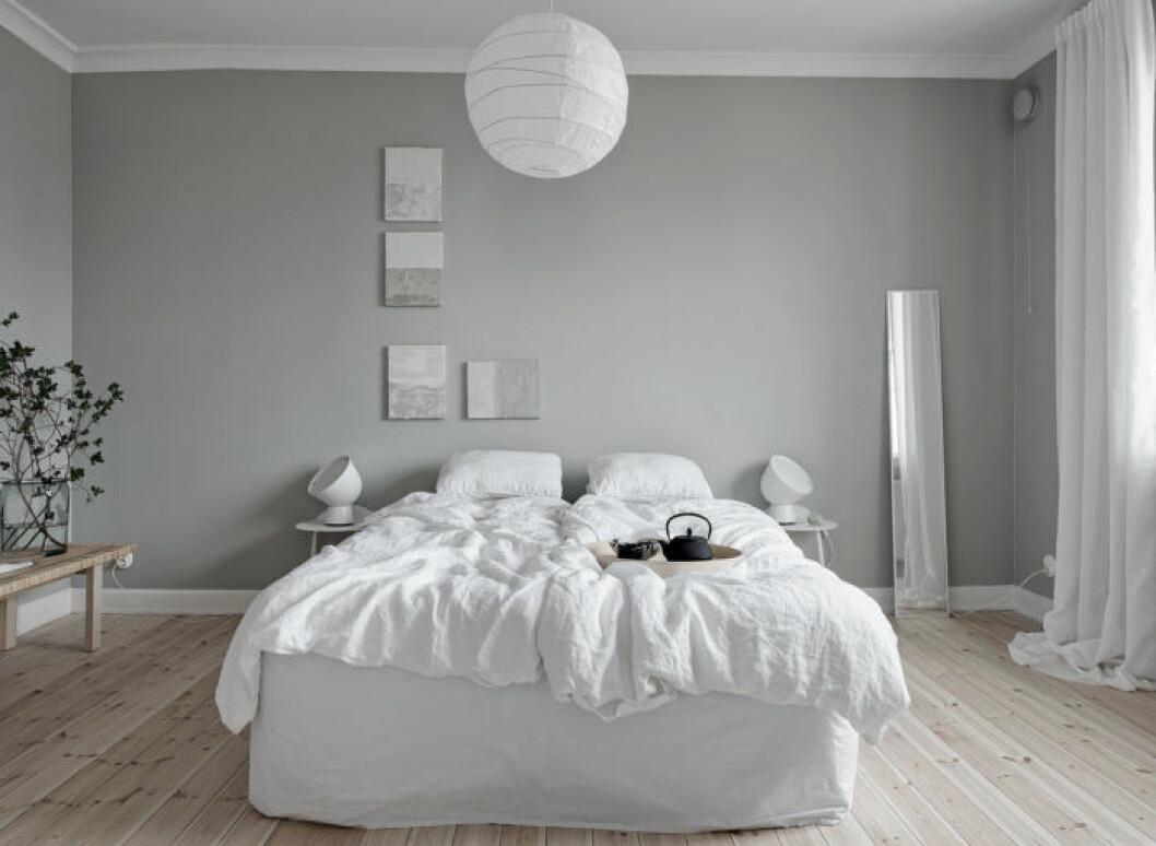 Sovrum med ljusgrå målade väggar.