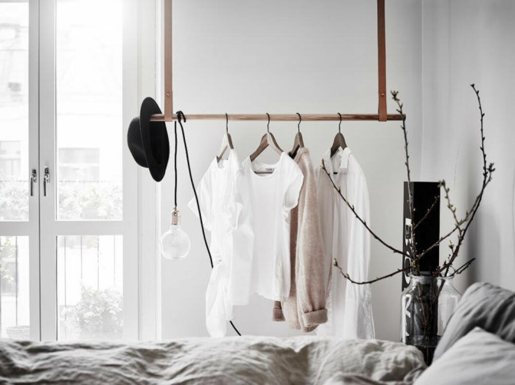 Sovrum med klädställning som hänger ner från taket med läderremmar.