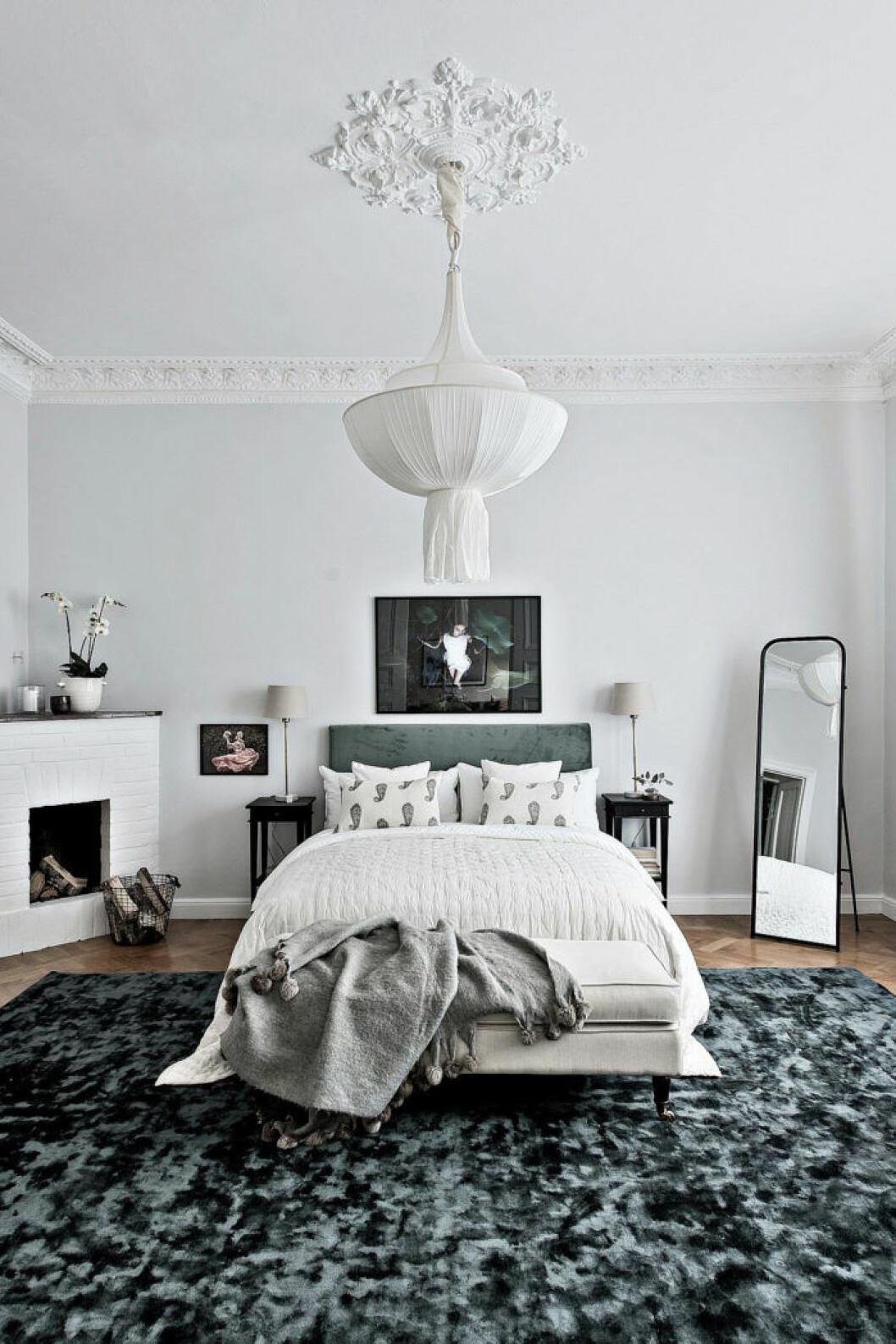 Sovrum med en stor dekorativ matta och en fin lampa i tyg