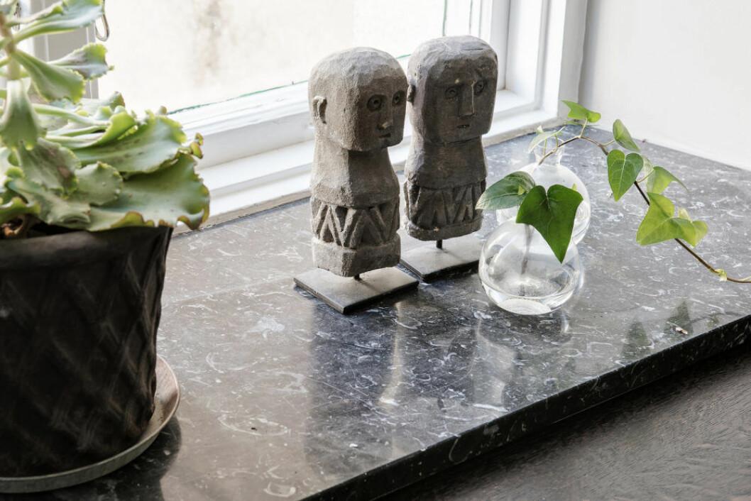 Fönsterbräda där små dekorativa skulpturer står sida vid sida med krukväxter och små minivaser