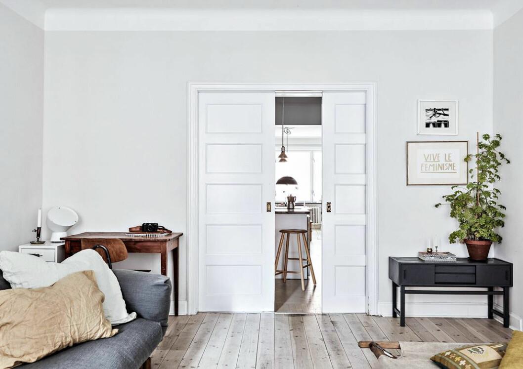 Vitt vardagsrum med skjutdörrar. Trägolv och doftpelargon på möbel.