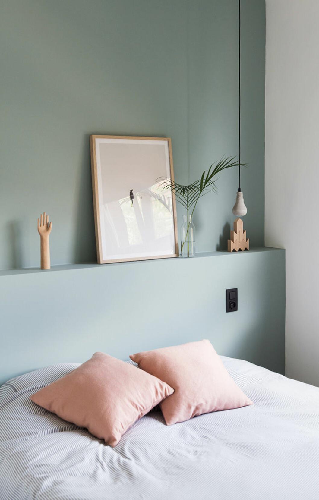 Sovrum med mintgröna väggar och rosa kuddar