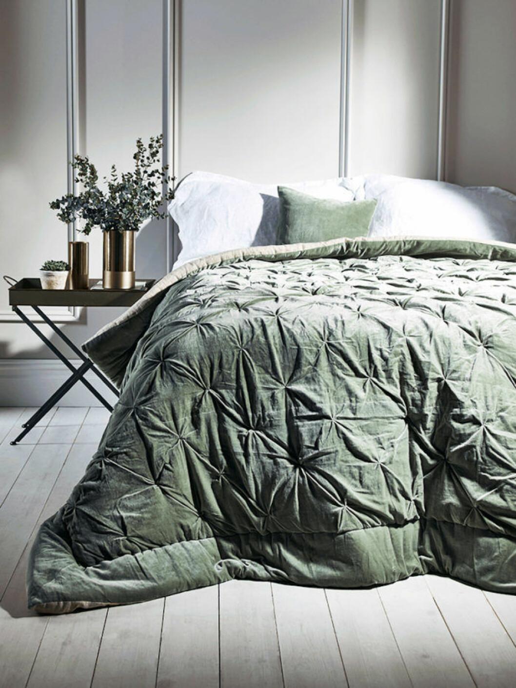 Sovrum med grönt sammetsöverkast och dekorationskudde