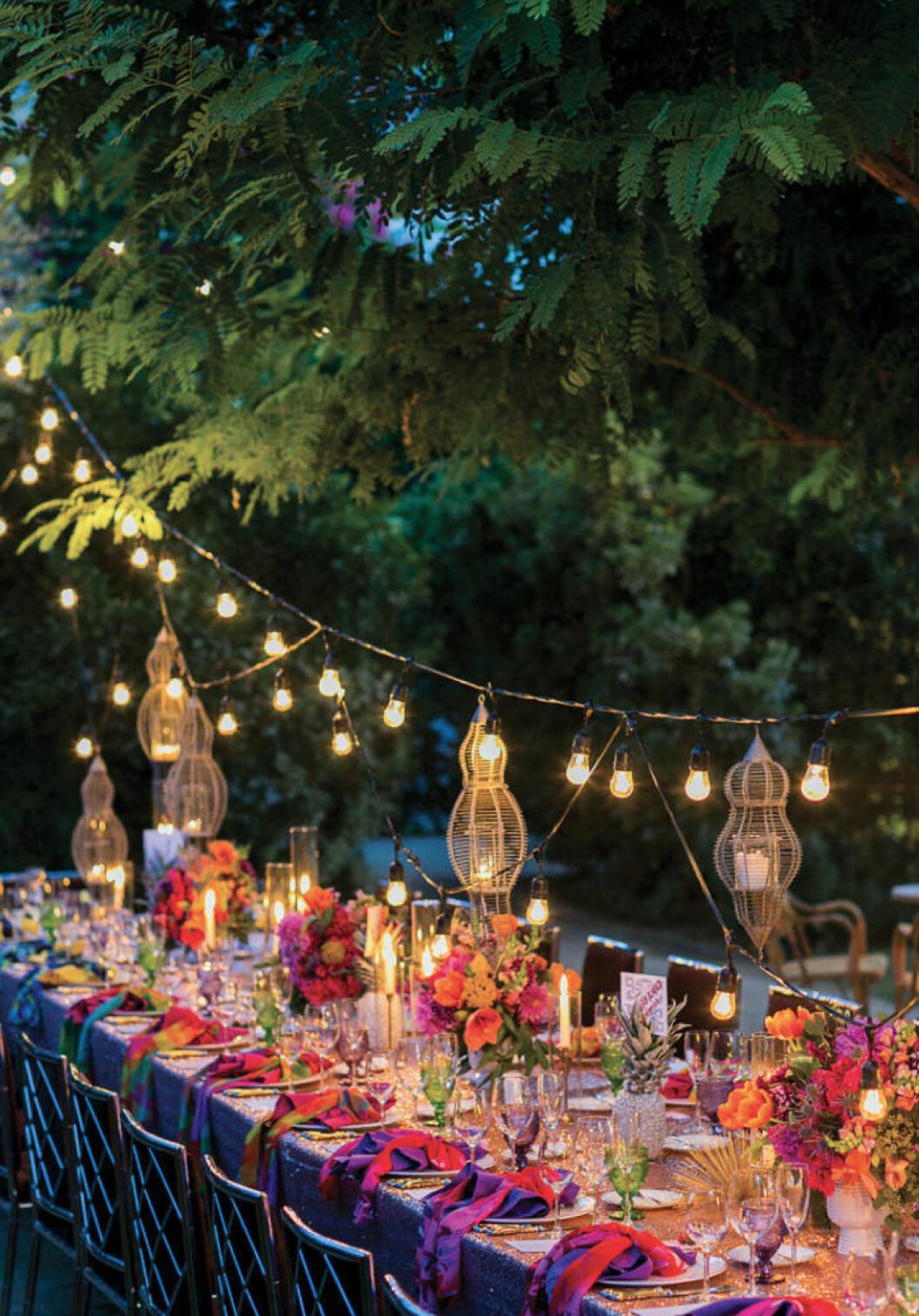 en färgglad dukning under träden förhöjs med ljusslingor
