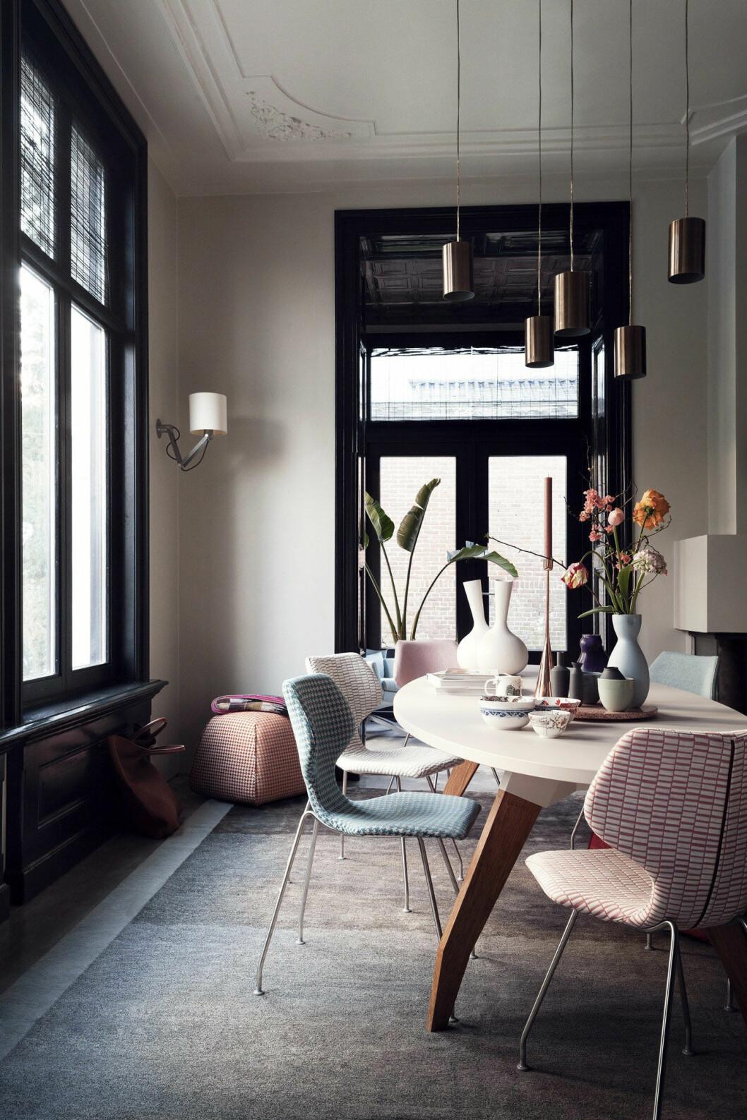 Pastellfärgade stolar i snygg kontrast mot de svarta, markerade fönsterkarmarna