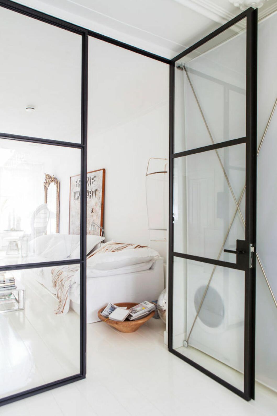 En glasvägg i industristil skärmar av på ett snyggt sätt i compact living-lägenheten.