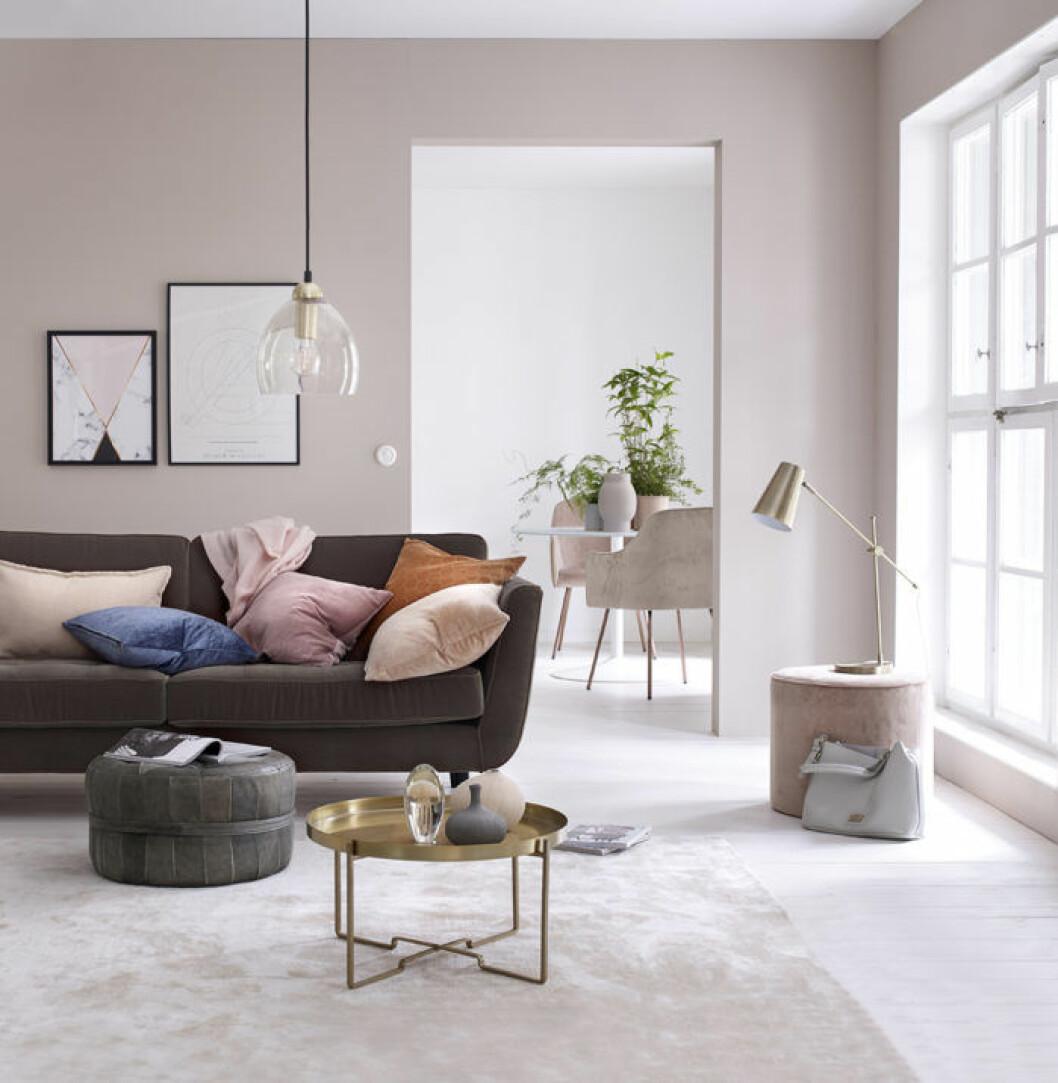 Ljusrosa väggfärg, brun soffa, brickbord guld. Rosa sittpuff i sammet. Våren 2018 på Ellos Home.