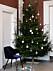Julgran med få, utvalda julkulor i vitt, blått och grått.