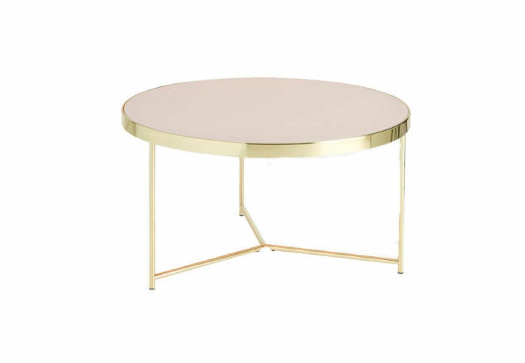 Runt soffbord med färgad skiva i rosa glas och stomme av guldfärgad metall.